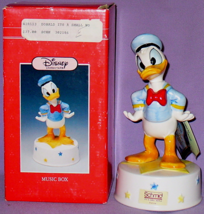 This Is An 8 Ceramic Musical Showing Donald Duck Standing With Both Arms Bent Akimbo On His Hips He Stands A Yellow Star That Appears Atop White